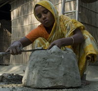 Sahena putting the finishing touches to a portable clay oven