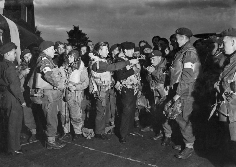 Paratroopers of 6th Airborne Division, including members of the Parachute Ambulance units, enjoy a last cigarette with RAF aircrew before boarding their transport