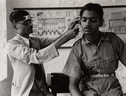 A doctor examines the ear of a trainee mechanic in the Indian Air Force at the Poona engineering college during the second world war.