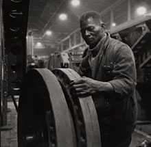 A technician from Jamaica fits a wheel to a tank in a north of England factory in World War Two