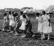 From album of Dr Joseph Fine, women line up in their dresses for sisters' three legged race, 1943.