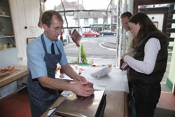 Photo showing a butcher wrapping some meat for a customer in a farm shop in Appleby-in-Westmoreland, Lake District