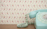Blue telephone against patterned wallpaper