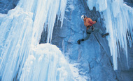 Man climbing up an icy rock face. © Peter Moynes/Getty Images