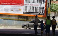 People walking near campaign poster against child sex tourism, Rio de Janiero. © VANDERLEI ALMEIDA/AFP/Getty Images