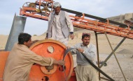 Three Afghan men working on a reconstruction project