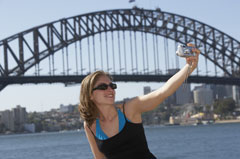 Girl taking a photo of herself in front of Sydney Harbour bridge (copyright Getty Images)