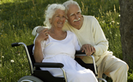 Senior woman in wheelchair, posing for photo with her husband. © Peter Teller/Getty Images