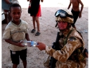 Royal Marine gives young Iraqi boy a bottle of water