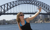 Girl taking a photo of herself in front of Sydney Harbour Bridge (Getty)