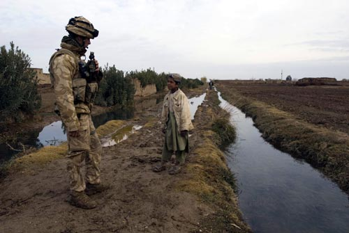A Royal Marine from Lima Company, 42 Commando Royal Marines Group talks to a young Afghan boy during operations in the Helmand province of Southern Afghanistan to bring security to the surrounding areas