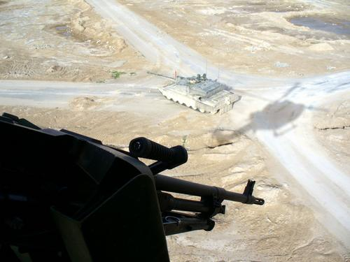 An 847 Lynx makes a low pass over an element of the British forces it is supporting in Iraq