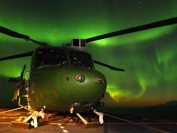 A Lynx Mk7 from 847 NAS on the deck of HMS Albion against the backdrop of the Northern Lights during EX JOINT WINTER 2004