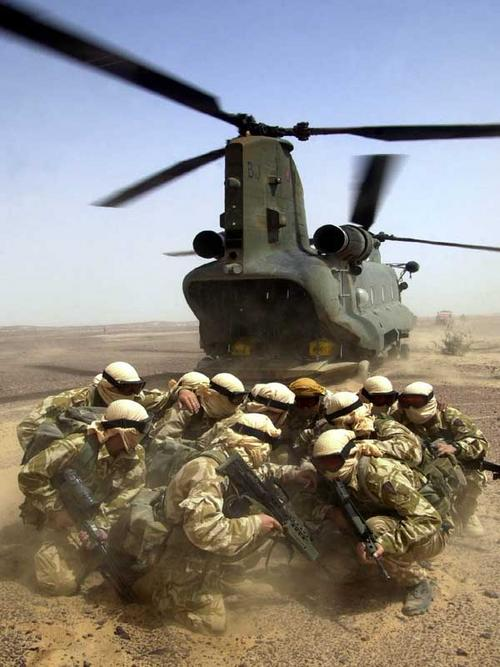 Royal Engineers from 59 Commando go into a huddle having just left an RAF Chinook helicopter during a training exercise in Oman on Exercise Saif Sarrea. The engineers are part of 3 Commando Brigade Royal Marines.