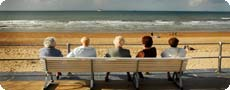 A group of older people sat on the seafront.