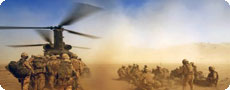 Troops and a military helicopter in the desert (MoD/Crown Copyright from www.defenceimages.mod.uk).