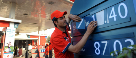 A Pakistani gas station employee adjusts a price board showing the newly fixed fuel prices in Karachi (Getty images)