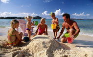 Parents and young children playing in sand at beach. © Steve Mason/Getty Images