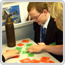 A teacher points to a resource on a table whilst two key stage 3 pupils look on