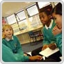 key stage 3 pupils sit together discussing whilst one transcribes