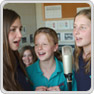 three key stage 3 pupils sing into a recording studio microphone