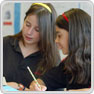 Two key stage 3 pupils doing written work together