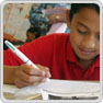 A key stage 3 pupil completes written work sitting at a desk
