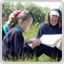 a small group of female key stage 3 pupils writing, sitting in grass on a sunny day
