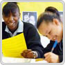 two female key stage 3 pupils sit at a desk smiling - one reads a piece of paper, the other writes