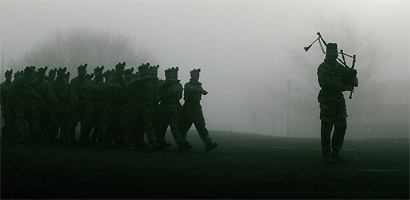 First sight through the mist, of the first group of married soldiers from the 1st Battalion The Black Watch, led by a lone piper as they march onto the square at Battlesbury Barracks, Warminster to be greeted by their families. The soldiers were the first
