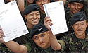 Gurkha soldiers proudly hold aloft their City and Guilds educational certificates for language training.