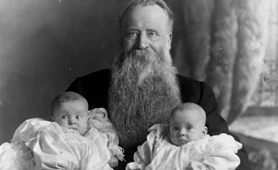 Photograph of Reverend Robert Small holding two babies, 1902 (Catalogue reference: COPY 1/458/220)