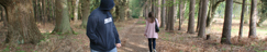 Picture of female walking alone through woodland being followed by a male in a hooded top
