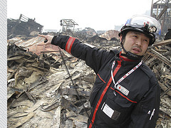 A Japanese Red Cross worker surveys tsunami damage in the city of Otsuchi. Image: IFRC