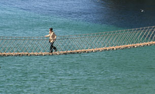 Image of person walking over rope bridge