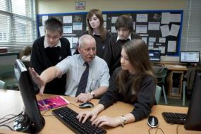 Teacher speaking to a group of pupils at a computer