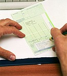 Doctor signing prescription after consultation