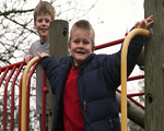Young boys playing on climbing frame