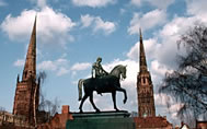 Statue of Lady Godiva with the spires of the Holy Trinity church and the ruined Coventry Cathedral
