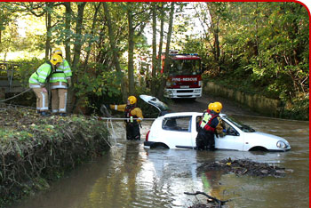 Firefighters rescue a car from fast flowing water caused by flooding