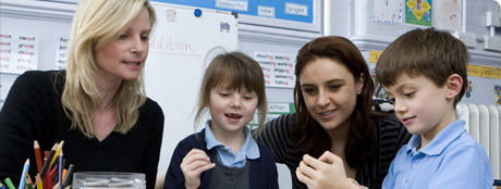 an image of teachers working with young pupils