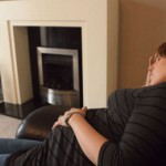 Pregnant woman asleep on sofa with heater in background