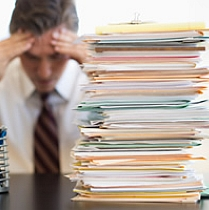 Man with his head in his hands sitting behind a pile of paperwork