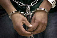 A pair of hands handcuffed together. Photo by Getty Images.