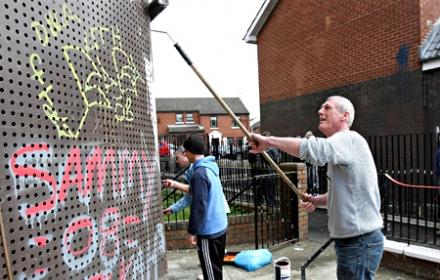 A community group removes graffiti. Photo: PA.