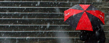 Red and black umbrella protects person from the snow