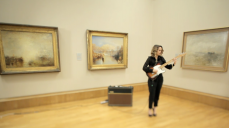 Ana Calvi playing an electric guitar in a gallery at Tate Britain