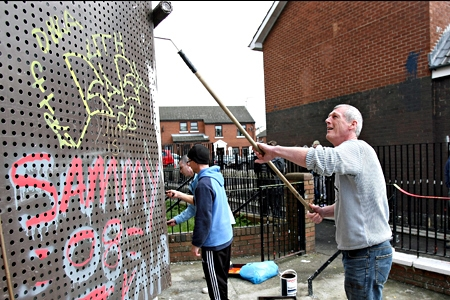 Volunteers cleaning graffiti from a wall. Photo: PA.