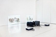 A video installation: two projections of groups of people on white walls with the projecting equipment in the centre of the room