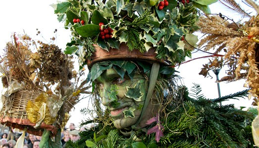 man with green painted face covered in holly